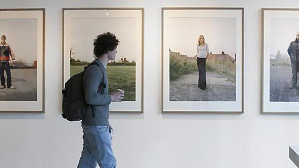 Photography student walking past gallery