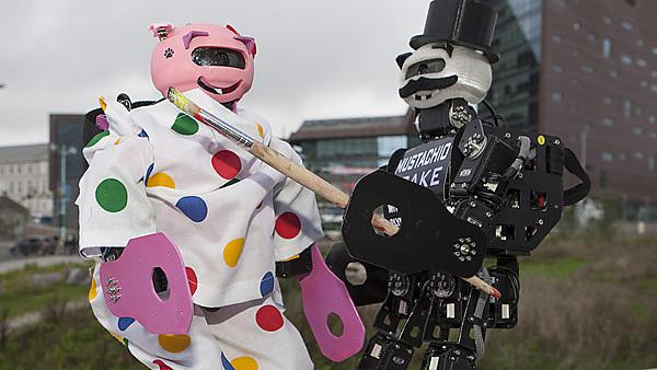 Humanoid robot Eva dressed as Pudsey for Children in Need. Mustachio adding the Wear your spot water tattoo as part of theGo Bear Faced initative.