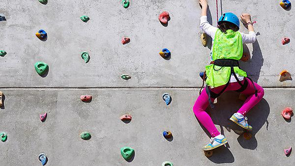 Child climbing up climbing wall, Image courtesy of Shutterstock