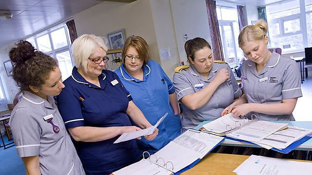 Nursing students working with qualified nurses and patients