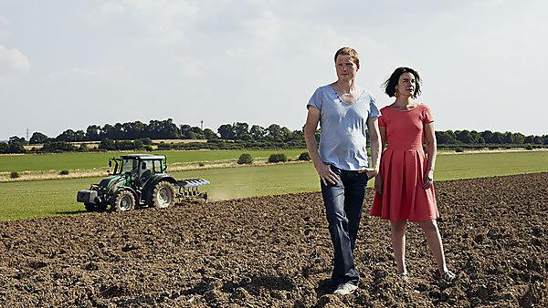 Manpower performance. Man and woman stood in a field with a tractor.