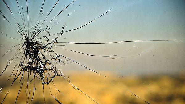 Broken window, cracked glass on urban background, courtesy of Shutterstock, Copyright: Borya Galperin