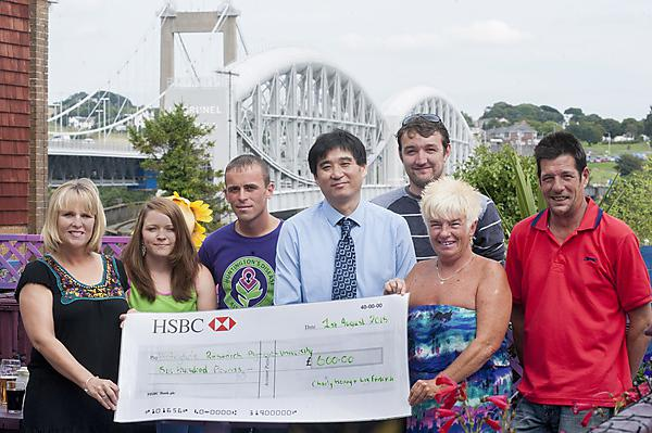 Dr Shouqing Luo, who heads up research into Huntington's disease at University of Plymouth, receiving a check from the organisers of last year's event