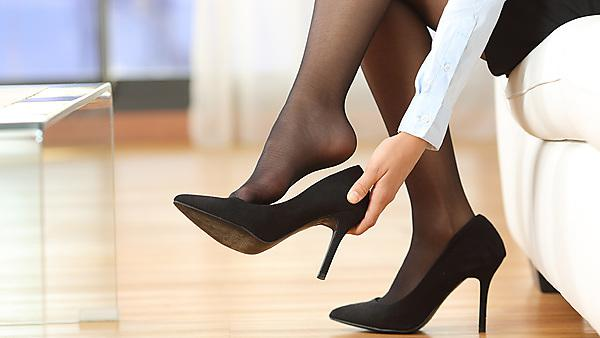 <p>Business woman taking off high heels.</p>