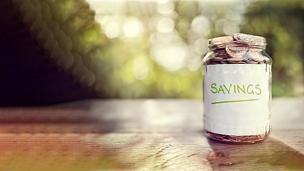 <p>Image of a glass jar with saving written on a label, full with coins.</p>