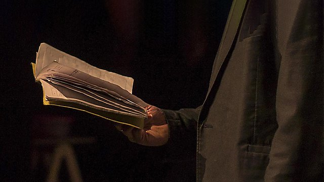 <p>A close-up image of a man reading from an open book</p>