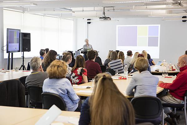 <p>Conference audience listening to