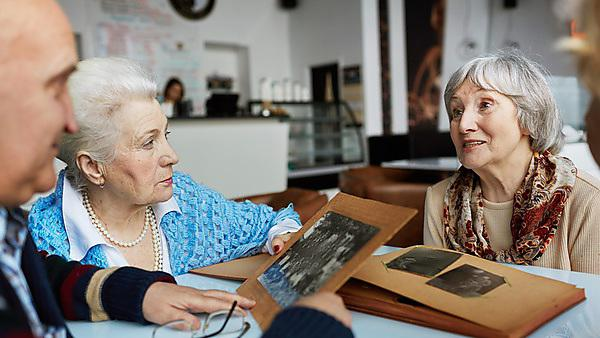 <p>Memories - friendly seniors talking while looking through photographs</p>