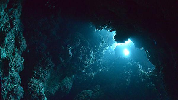 <p>Cave diving – sunbeam into the dark cave</p>
