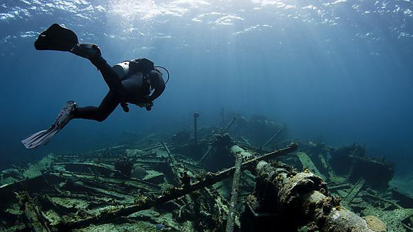 <p>A scuba diver swims over a sunken shipwreck<br></p>