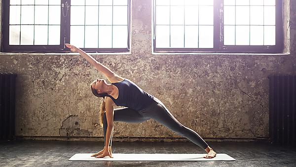<p>Young woman practicing yoga in an urban loft.<br></p>