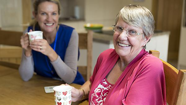 <p>Community care worker joins an an elderly woman for a cup of tea while sitting at her kitchen table.<br></p>