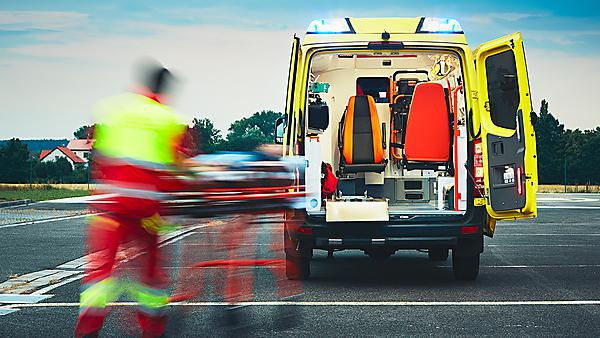 <p>Emergency medical service. Paramedic is pulling stretcher with patient to the ambulance car.<br></p>