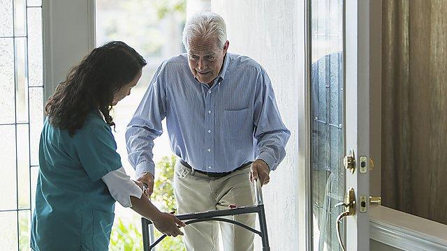 <p>Home healthcare worker helping elderly man with walker.<br></p>
