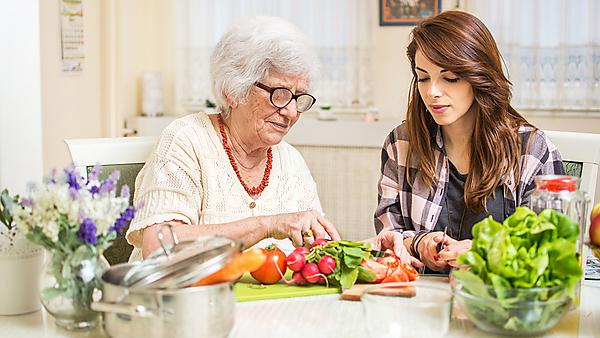 <p>Grandmother and granddaughter preparing food together at kitchen.<br><br></p>