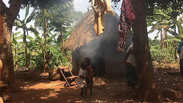 <p>Children by smoky hut in Uganda</p>
