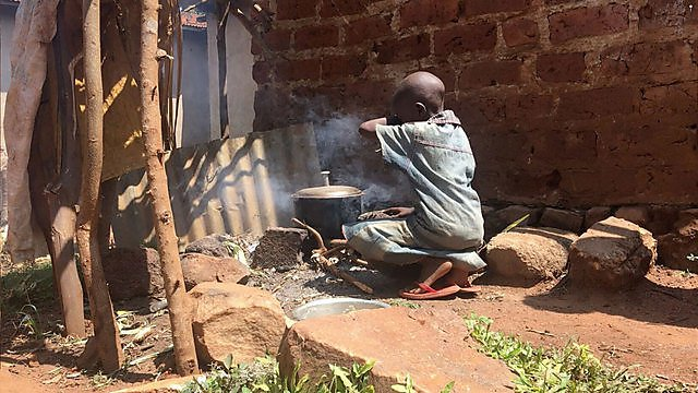 <p>Child cooking by a smoky pot in Uganda</p>