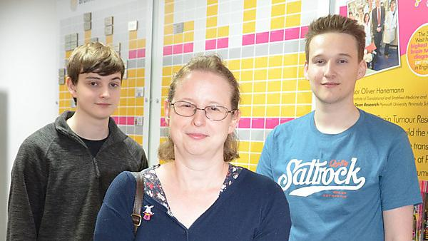 <p>Michael Legg (right) with mum Julie and brother Jamie by the University of Plymouth Brain Tumour Research Centre of Excellence Wall of Hope<br></p>