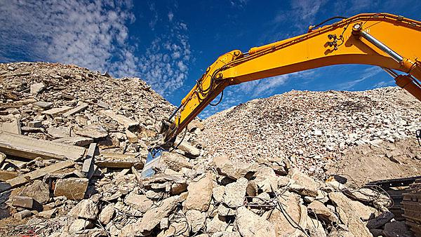Construction and concrete demolition waste recycling site with excavator boom.