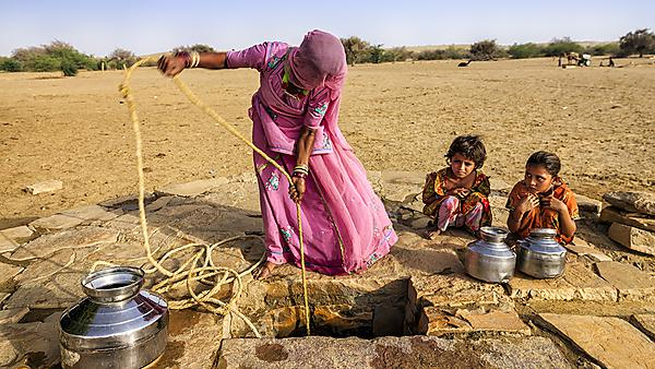 <p>Indian woman drawing water from the well in the desert, Rajasthan, India.</p>