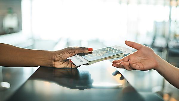<p> handing over passport at a boarding gate in an airport<br></p>