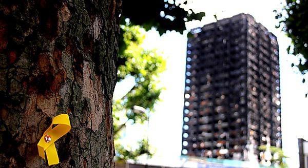 <p>Grenfell Tower in the background with a Yellow Ribbon commemorating those lost pinned to a tree<br></p>