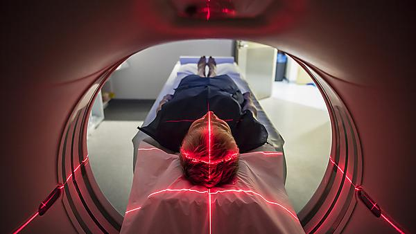 <p>Patient lying inside a medical scanner in hospital.<br>CAT scan in hospital. <br>PET scan equipment. <br>Medical CT scan of patient.</p>