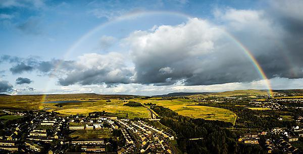 <p>Aerial view of a rainbow over a small Welsh town<br></p>