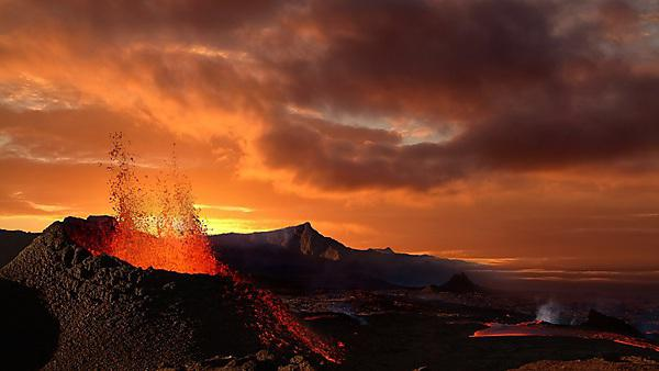 <p>Volcano erupting at night spewing orange lava<br></p>