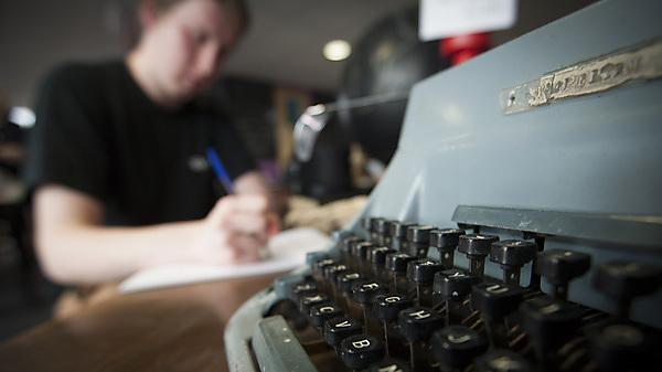 Typewriter and student writing