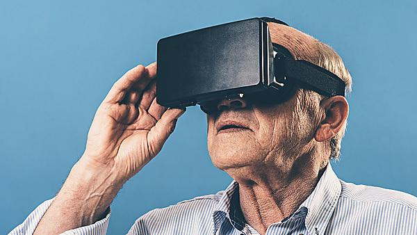 <p>VR glasses worn by senior man. He adjusts the content shown before his eyes by pushing buttons on the side of the device.<br></p>