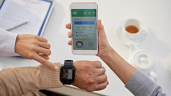 <p>Young physician wearing white coat explaining senior patients how to use mobile application in order to control heart rate while having consultation at office<br></p>
