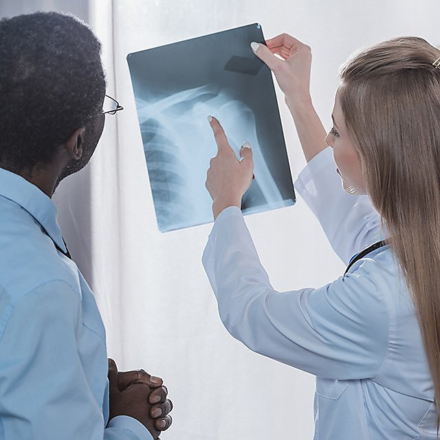 <p>A doctor showing an x-ray to a patient.<br></p>