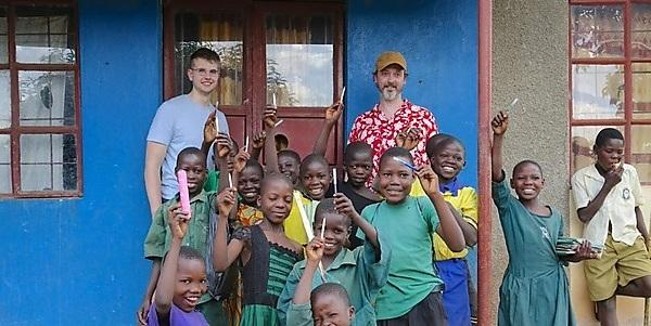 <p>Angus Ulyett and John Kilburn with children in Uganda</p>
