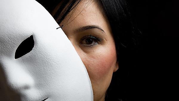 <p>A young woman with black hair and black eyes looking at the camera from behind a white mask.<br></p>