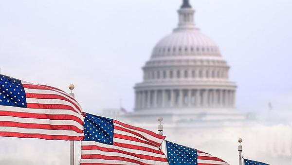 <p>United States flags with Capitol building in Washington, DC on background.<br></p>