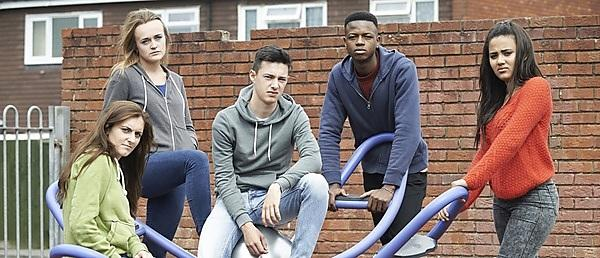 <p>Gang of teenagers hanging out in children's playground</p>
