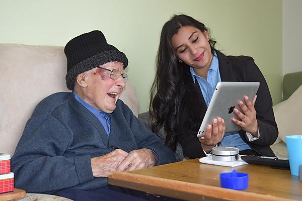 <p>Sonam Zamir shows Skype to care home resident</p>
