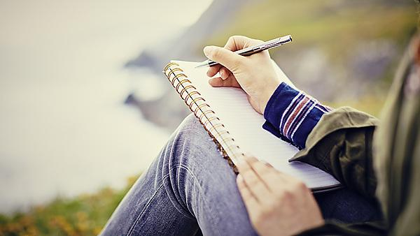 <p>Writing in a notepad on the cliffs overlooking a beach</p>