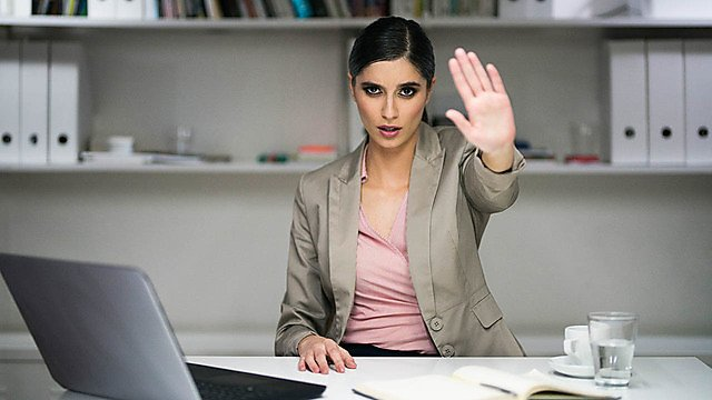 <p>A women in an office environment gesturing the stop sign with her palm.</p>