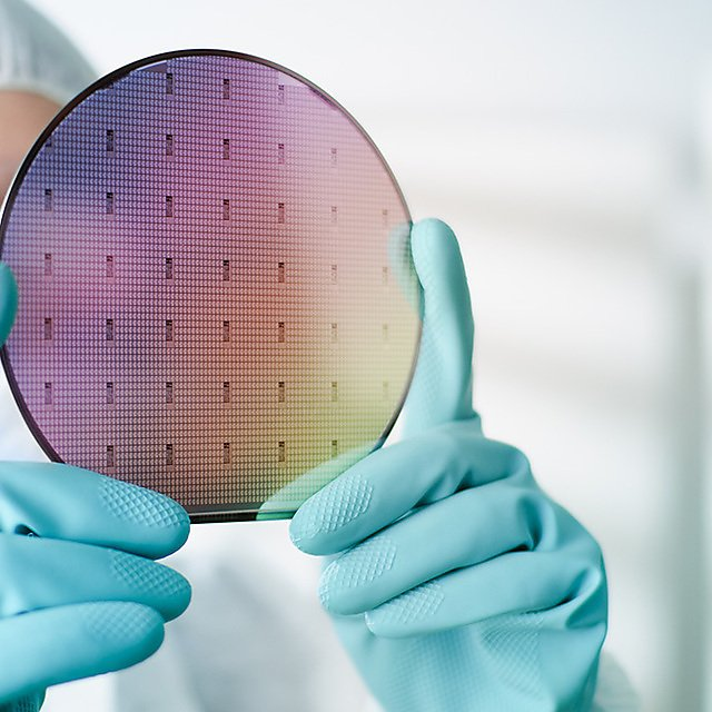 <p>Lab worker examining a silicon wafer<br></p>