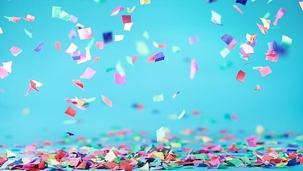 <p>Coloured confetti against a blue background</p>