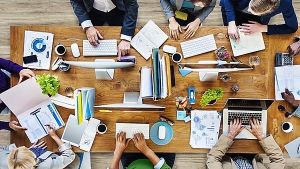 <p>Overhead view of colleagues at work on one table</p>