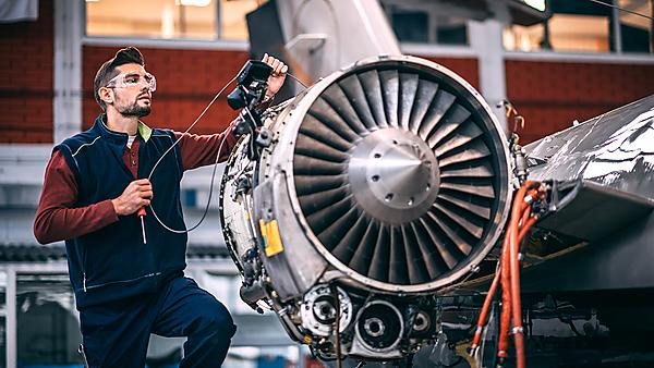 <p>Aircraft engineer in a hangar holding a camera probe while repairing and maintaining airplane jet engine <br></p>