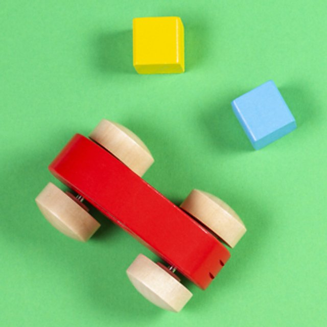 <p>Colourful wooden cars and cubes on green colour background.<br></p>