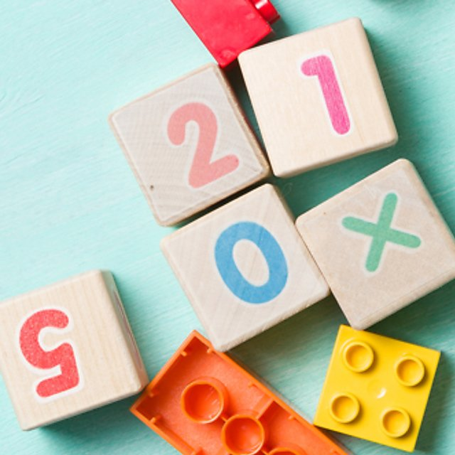 <p>Wooden cubes with numbers and colourful toy bricks on a turquoise wooden background.<br></p>