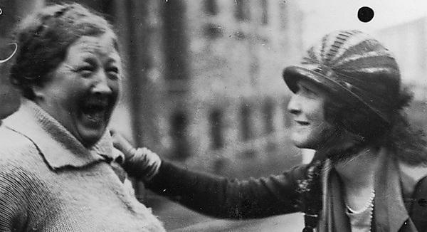<p>Nancy Astor talking to a woman on a street in Plymouth</p>