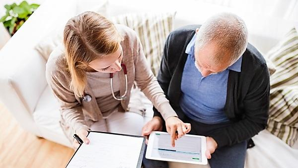<p>Health visitor and a senior man with tablet during home visit</p>