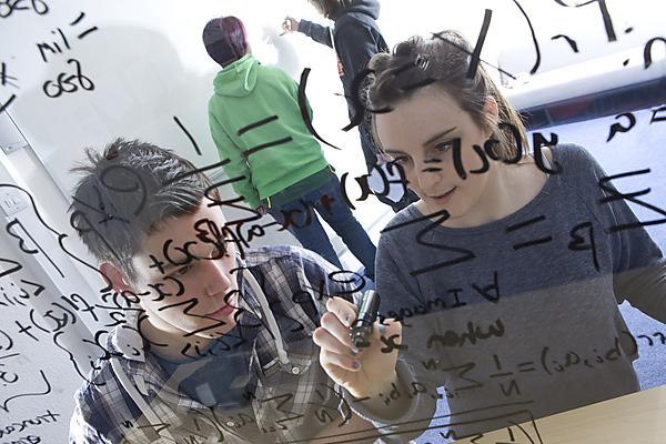 Students writing maths formulae on glass