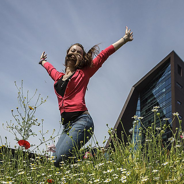 Student jumping with Roland Levinsky Building in the background